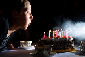 blowing out candles on cake