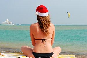 woman is sitting near sea in santa hat