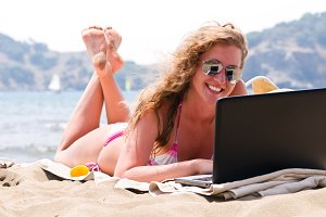 happy woman is working on laptop on beach