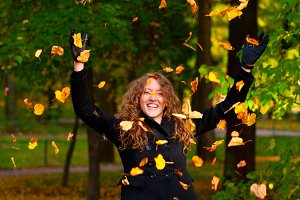 throwing dry autumn leaves in park
