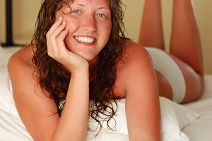 woman is smiling in bedroom