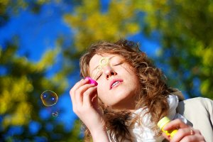 young fresh woman blowing bubbles
