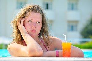 sad pretty bored woman is boring in the hotel swimming pool
