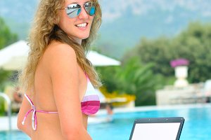 woman is sitting with laptop on the edge of swimming pool under