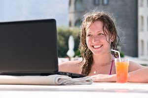 woman is using laptop from swimming pool near the hotel