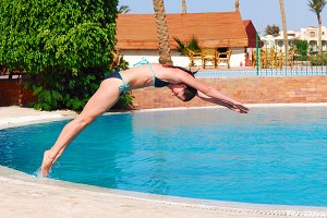 woman jumping into the pool