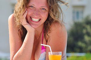 smiling woman in pool with cocktail