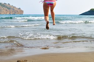 excited woman is running to the sea