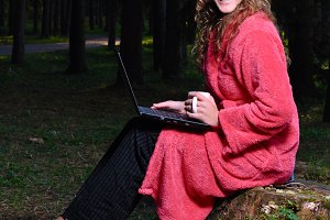 happy woman is working on laptop at forest in undress