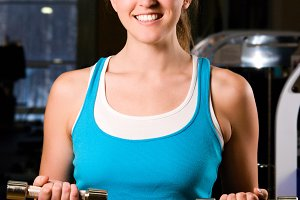beautiful woman is exercising in gym at evening
