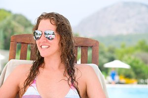 smiling woman is sitting on chair at poolside