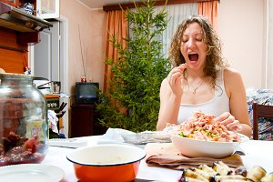 young woman is cooking holiday food and tasting it