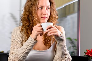 young woman is sitting at cafe