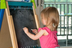 Young baby girl painting at easel