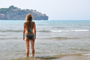 woman is standing at sea coast with sand on her back