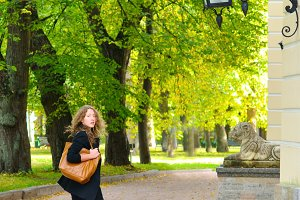 woman is walking at autumn city park