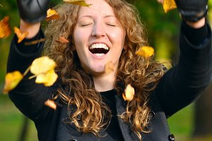 happy woman is throwing dry autumn leaves in park