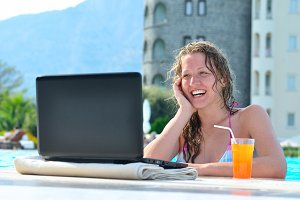 beautiful woman is using laptop in the swimming pool