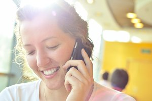 beautiful smiling woman is talking phone  and looking downwards