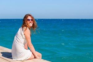 beautful woman sitting on the pier