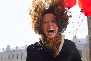 laughing woman with red balloons on spring city street