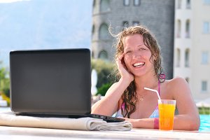 beautiful woman is using laptop at poolside