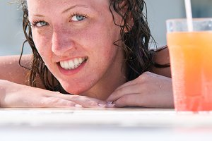 close up of pretty woman with wet hair in swimming pool with coc