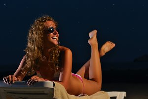 happy woman is lying on the night beach