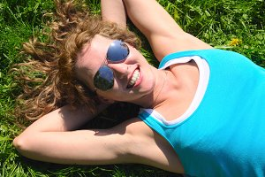 smiling woman is lying on grass