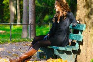 young woman is sitting on the bench in autumn park and looking s