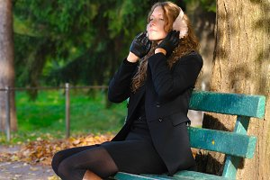 young woman is sitting on the bench in autumn park and listening