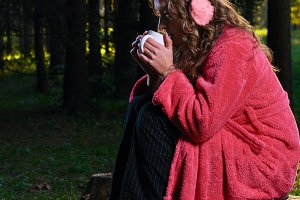 woman is sitting in bathrobe in the forest and drinking from a m