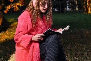 happy woman is reading magazine at forest in undress