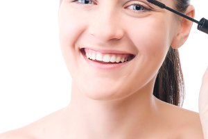 smiling woman is applying mascara