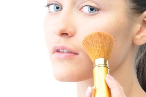 young attractive sensual woman is applying cosmetics on her face