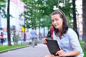 beautiful woman is sitting in city with laptop and looking at ca