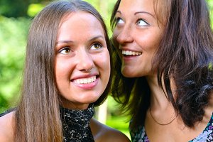 two female friends are sharing secrets in summer park