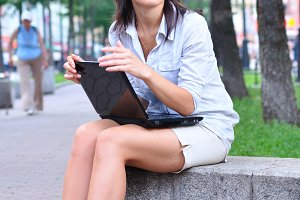 beautiful woman is sitting in an alley with laptop and looking s
