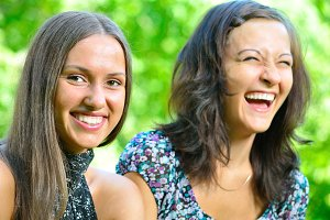 two female friends is laughing in sunny park