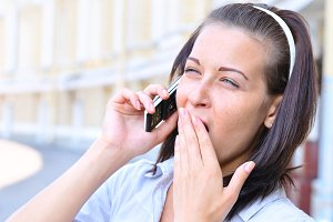 woman is talking phone and yawning