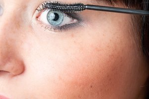beautiful woman applying mascara. A lot of copy space