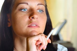 woman is smoking at cafe and looking sideways