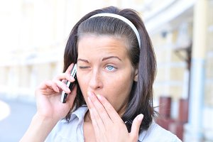 funny woman is yawning when talking phone