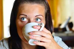 young woman is drinking coffee in cafe and looking sideways