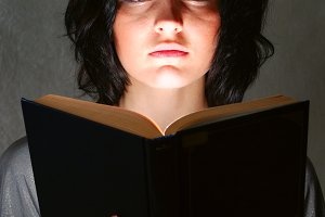 young beautiful woman is illuminated by a glowing book