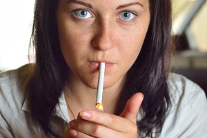 young woman is lighting a cigarette in a cafe