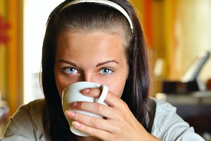young woman is drinking coffee in cafe and looking at camera