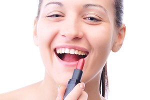 young laughing woman is applying cosmetics on her face and looki