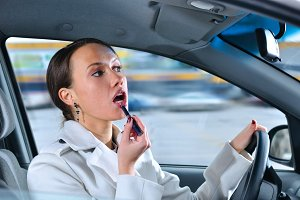 elegant woman is doing makeup on the run in her car