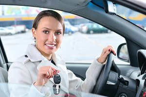happy woman is showing keys of her new car